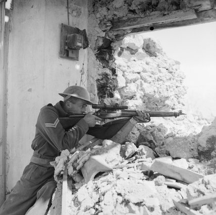A New Zealander poses with his sniper rifle in the ruins of Cassino, 26 March 1944.