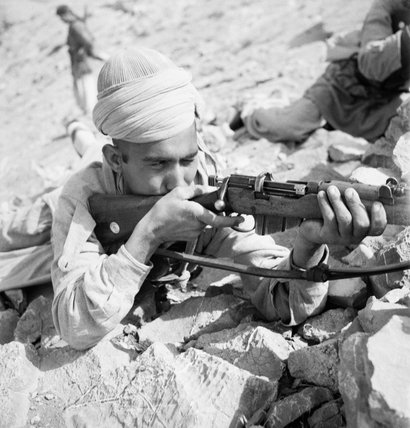 Cecil Beaton portrait of an Indian Tochi Scout firing his Lee Enfield rifle on the North West frontier of India, circa 1944.