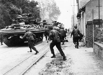 Sherman DD tanks of 'B' Squadron, 13th/18th Royal Hussars support men of No. 4 Army Commando on the Rue de Riva- Bella in Ouistreham, 6 June 1944.