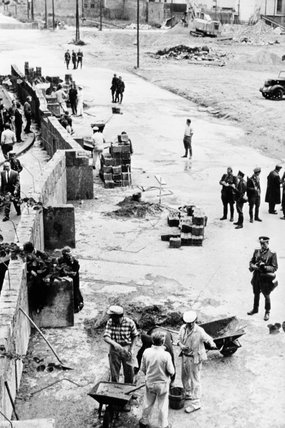 East German construction workers, supervised by East German border guards, build the Berlin Wall, 1961.