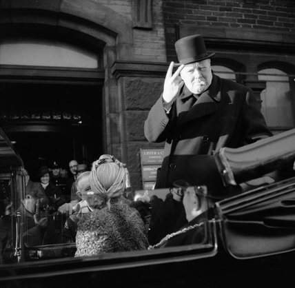 Winston Churchill, cigar in mouth, gives his famous 'V' for victory sign during a visit to Bradford, 4 December 1942.