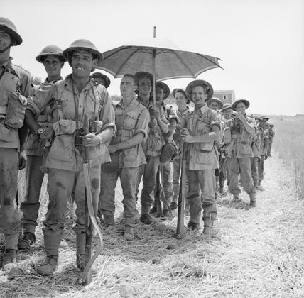 Men of the 6th Battalion, The Royal Inniskilling Fusiliers, 78th Division, await orders to move into Centuripe, Sicily, 2 August 1943.
