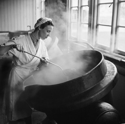 An Auxiliary Territorial Service (ATS) cook at work in an army cookhouse, stirring a large cauldron of stew, 10 December 1942.