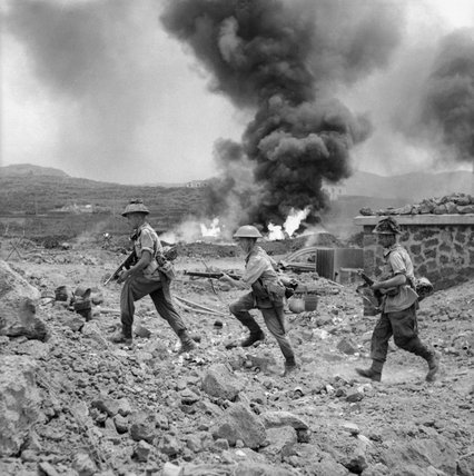 Men of 1st Battalion, The Duke of Wellington's Regiment advance past a burning fuel store on Pantelleria in the Mediterranean, 17 June 1943.