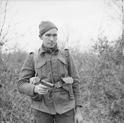 Private W Stack of No. 9 Commando at Anzio, equipped for a patrol with a Browning pistol, 5 March 1944.