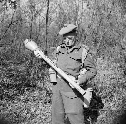 Captain W Guest-Gordons, Intelligence Officer with No. 2 Infantry Brigade, examines a German Panzerfaust anti-tank weapon, Anzio, 27 February 1944.