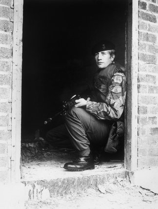 A soldier of 1st Battalion, The Royal Welch Fusiliers crouched in the doorway of a deserted building during a patrol in the Ligoniel area of North Belfast, May 1977.