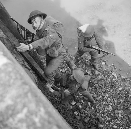 Men of the South Staffordshire Regiment climb up onto a harbour wall during an amphibious exercise in Northern Ireland , 24 April 1942.