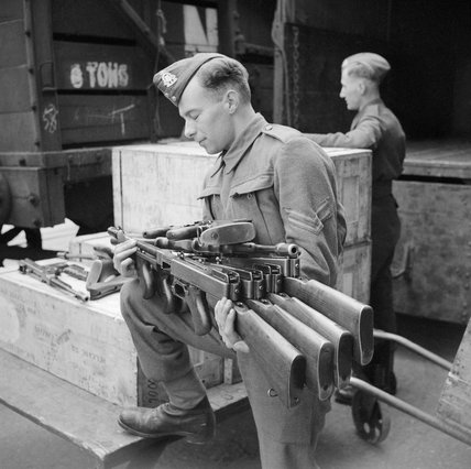 Thompson submachine guns, or 'Tommy guns', being un-crated at an ordnance depot in the UK after their arrival from the US through the Lend-Lease scheme, 23 March 1942.