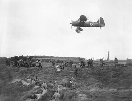 A Westland Lysander of No. 13 Squadron RAF based at Hooton Park, Cheshire, provides aiming practice for members of the Home Guard, at the Western Command Weapons Training School at Altcar, near Formby, 17 September 1940.