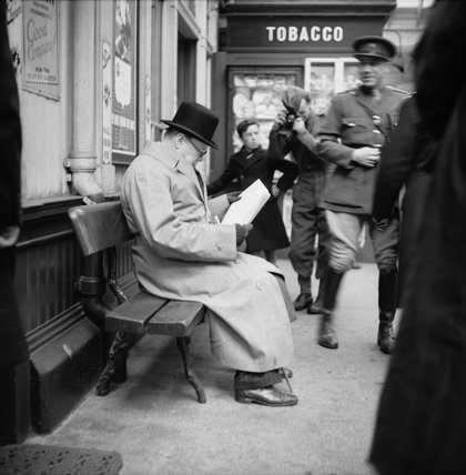 Winston Churchill reads a newspaper on the platform at St Andrews railway station, during a tour of defences and naval forces in Scotland, 23 October 1940.