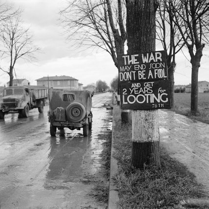 A British jeep passes a sign warning against looting on the outskirts of Ravenna, Italy, 7 December 1944.