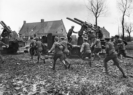 Men of an Anti-Aircraft Section near Armentieres rushing to their guns on the approach of hostile aircraft, March 1916.
