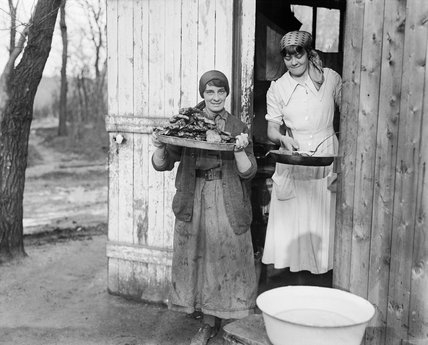 Two cooks of the First Aid Nursing Yeomanry (FANY) outside their hut with trays of food at a military hospital at Calais in January 1917.