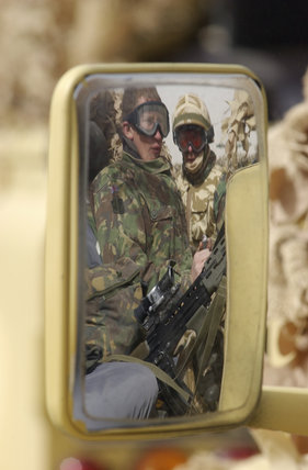 British soldiers seen in the wing mirror of a Landrover in Kuwait, February 2003.