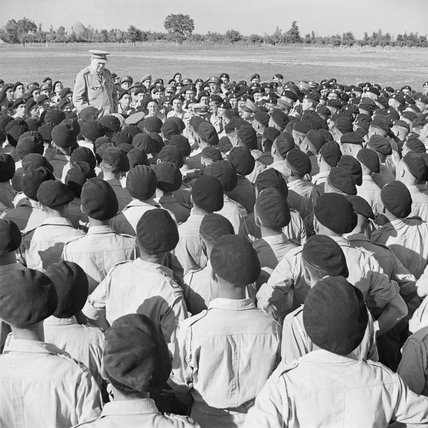 Winston Churchill delivers an informal speech to men of his old regiment, the 4th Queen's Own Hussars, at Loreto aerodrome in Italy, 25 August 1944.