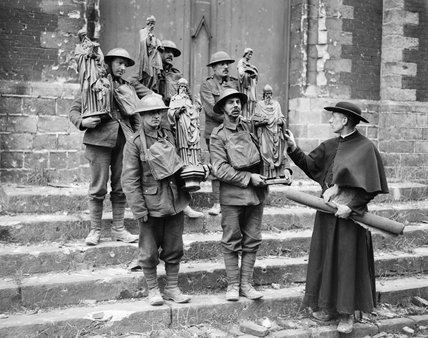 British soldiers help a French priest move statues from his shell-damaged church in Armentieres, 26 February 1918.
