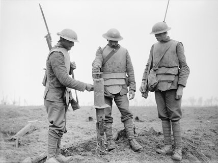 Three Irish Guardsmen wearing German body-armour, examining a captured machine-gun near Pilckem, 31st July 1917, during the Third Battle of Ypres.