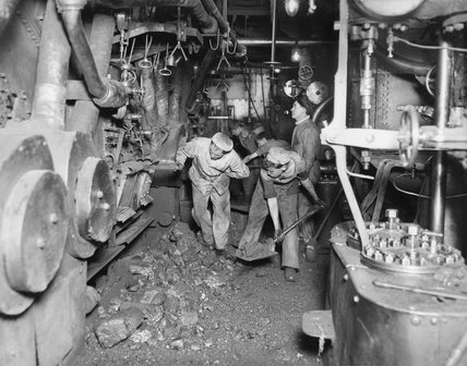 Stokers shovelling coal into the enormous boilers of a British battleship in 1917.