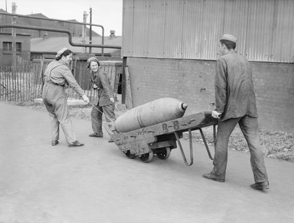 Three munitions workers transport a large bomb on a wheelbarrow at a British munitions factory in 1941.