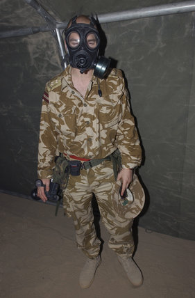 Leader of the Army Mobile News Team, photographed wearing a gas mask and holding his camera during an NBC (Nuclear Biological and Chemical Weapons) alert at 33 Field Hospital, Iraq, 18 February 2003.