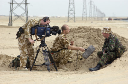 Sergeant Stuart McKenzie and Captain Guy Gatenby of the Army Mobile News Team, film an interview with a REME soldier attached to 6 Supply Regiment Royal Logistics Corps, at Camp Fox in the Kuwaiti desert, 11 Febraury 2003.