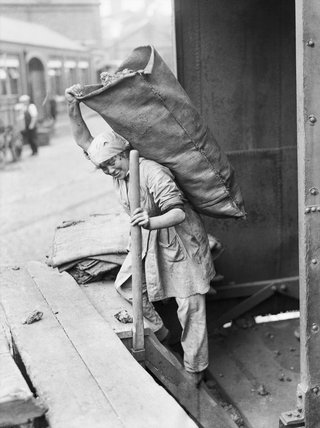 A woman war worker carrying a sack of coal at the South Metropolitan Gas Company, Old Kent Road, London, 1918.