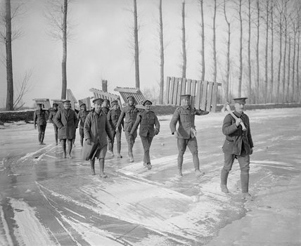 Members of a Royal Garrison Artillery working party carrying duck-boards across the frozen Somme canal at Frise in March 1917.
