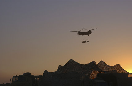 A British Army helicopter carries a load over a camp at sunset in Kuwait, during preparations for Operation 'TELIC', the invasion of Iraq, 2003.