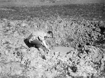 British soldier washing in a shell hole on the Western Front, 21 April 1917.