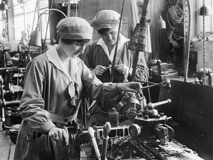 Two women workers operate machinery at Armstrong Whitworth and Co. shipbuilders and ordnance manufacturers at Elswick, Newcastle-upon-Tyne, during the First World War.