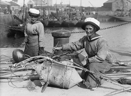 Two WRNS painting mines and steel floats on the quayside at Lowestoft in 1918.