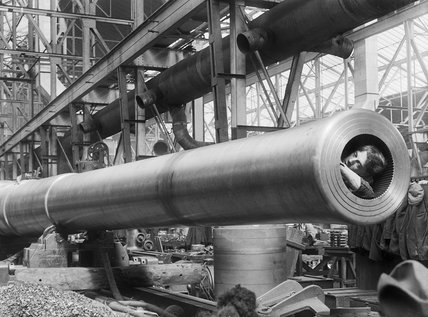 A female worker at the Ordnance Works in Coventry during the First World War cleans the rifling inside a newly manufactured naval gun.