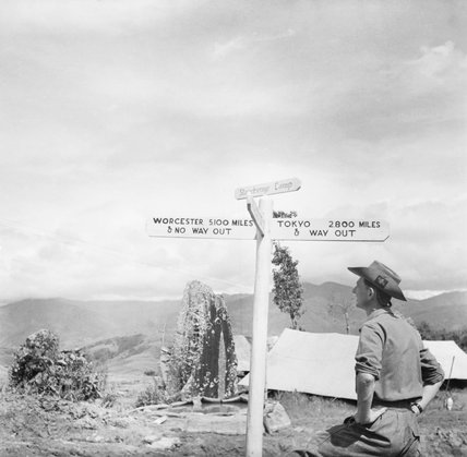 A member of the Worcestershire Yeomanry views an amusing roadsign at 'Stonehenge Camp' on the Imphal to Kohima road, Burma, November 1944.