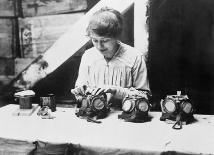 A woman war worker fixes nose clips on to gas masks at a factory in Bermondsey, London, 1918.