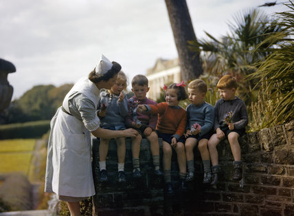 A nurse with child evacuees from Plymouth in the garden of the Chaim Weizmann Home at Tapley Park, Instow, North Devon, October 1942.