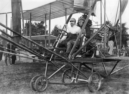 Samuel Cody at the controls of a Cody aircraft Mk II with a Native American in traditional dress as a passenger, c. 1910.