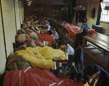 Members of the Womens Auxiliary Air Force (WAAF) repair and pack parachutes for use by airborne troops during the Normandy invasion, 31 May 1944.