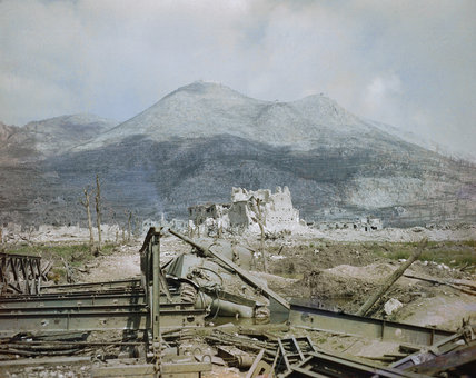 The ruins of Cassino, May 1944: a wrecked Sherman tank and Bailey bridge in the foreground, with Monastery Ridge and Castle Hill in the background.