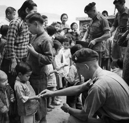 Men of 44 Royal Marine Commando hand out sweets from their 'compo' rations to local children on Cheung Chau Island, Hong Kong, 20 February 1946.