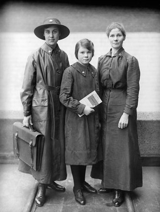 Three women War Office workers during the First Wold War: (left to right) an outdoor messenger, an indoor messenger and a supervisor.