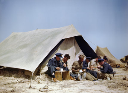 Spitfire pilots of No. 417 Squadron, Royal Canadian Air Force, having a meal outside a tent at Goubrine in Tunisia, April 1943.