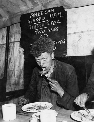 A Liverpool dockyard worker enjoys a meal of American baked ham during a working day in 1941.