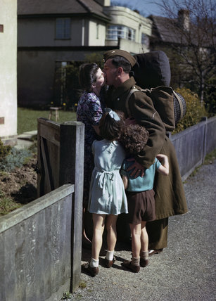 Lance Bombardier Jack Grundy of the Royal Artillery embraces his wife Dorothy and children Randall and Gilda at his home in Irby in Cheshire, at the start of seven days leave, 14 April 1944.