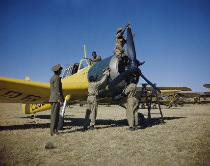 Basuto 'hangar boys' clean and polish a Miles Master at No. 23 Air School at Waterkloof in Pretoria, South Africa, January 1943.