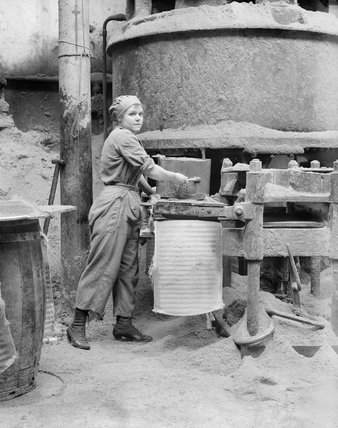 A woman war worker forms oil cake before placing it into a press at an oil works in Lancashire during the First World War.