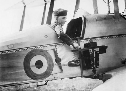 A sergeant of the Royal Flying Corps demonstrates a C type aerial reconnaissance camera fixed to the fuselage of a BE2c aircraft, 1916.