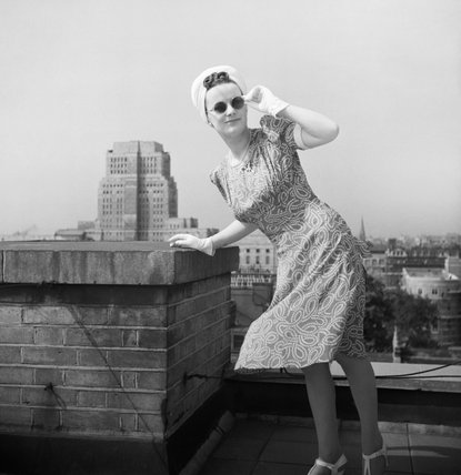 A model poses for the camera on a Bloomsbury rooftop as she shows off a cyclamen and white printed silk dress, the skirt blown by the breeze, worn with a white turban and white gloves. She is also wearing sunglasses.