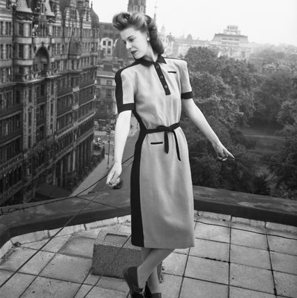 A model stands on a Bloomsbury rooftop, holding on to wire railings as she leans slightly backwards, to show off her pale blue and black wool Atrima dress, costing 11 coupons.