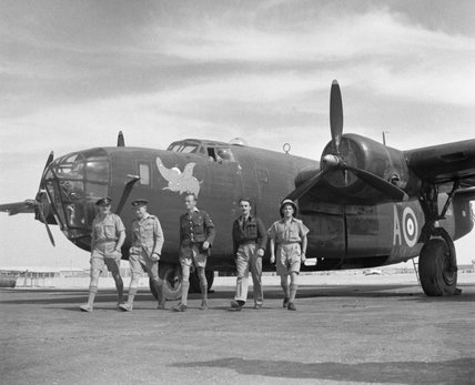The crew of Consolidated Liberator Mark II, AL511 'A', of No. 108 Squadron RAF walk from their aircraft at Fayid, Egypt.  Note the